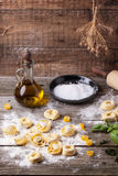 Pasta ravioli on flour. Homemade pasta ravioli on old wooden table with flour, olive oil and plate of salt Stock Photography