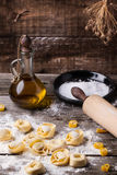 Pasta ravioli on flour. Homemade pasta ravioli on old wooden table with flour, olive oil and vintage rolling pin Stock Photography