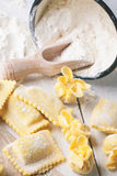 Pasta ravioli on flour. Homemade pasta ravioli and perle on wooden table with metal mug of flour Royalty Free Stock Photo