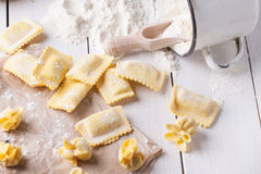 Pasta ravioli on flour. Homemade pasta ravioli and perle on wooden table with vintage mug of flour Royalty Free Stock Photo
