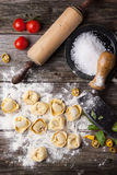 Pasta ravioli on flour. Top view on homemade pasta ravioli on old wooden table with flour, basil, tomatoes and vintage kitchen accessories Stock Image