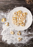 Pasta ravioli on flour. Top view on plate of homemade pasta ravioli over wooden table with flour Royalty Free Stock Photo