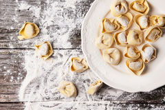 Pasta ravioli on flour. Top view on plate of homemade pasta ravioli over wooden table with flour Royalty Free Stock Image