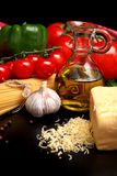 Pasta raw  on black with tomatoes,olive oil,garlic horiz Stock Image
