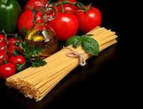 Pasta raw  on black with tomatoes,olive oil,garlic Stock Image