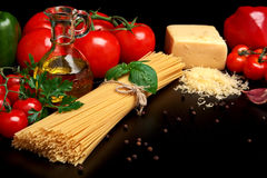 Pasta raw  on black with tomatoes,olive oil,garlic Stock Photo