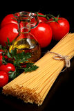 Pasta raw  on black with tomatoes,olive oil,garlic verti Royalty Free Stock Photos