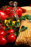 Pasta raw  on black with tomatoes,olive oil,garlic verti Royalty Free Stock Images