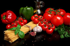 Pasta raw  on black with tomatoes,olive oil,garlic verti Stock Photos