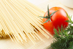 Pasta (raw spaghetti) with tomato on cutting board Royalty Free Stock Photo