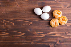 Pasta raw three circles and three white eggs on a brown wooden t Royalty Free Stock Images