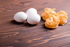 Pasta raw three circles and three white eggs on a brown wooden t Stock Image