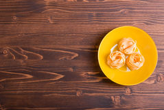Pasta raw three circles in yellow plate on brown wooden table to Royalty Free Stock Images