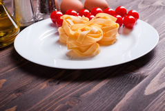 Pasta raw three slices and a sprig of cherry tomatoes on a white Royalty Free Stock Images