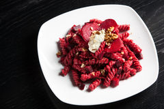 Pasta with Red Beets Cheese and Walnuts. A course of pasta with red beets a dollop of gorgonzola cheese and a sprinkle of crushed walnuts on top. Served on a Royalty Free Stock Images