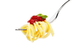 Pasta with red sauce and basil on a fork side. Pasta with red sauce and basil on a fork on white background Stock Photo