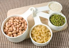 Pasta, Rice, Peanuts And Mung Beans In Measuring Spoons Royalty Free Stock Photo