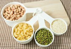 Pasta, Rice, Peanuts and Mung Beans in Measuring Spoons Stock Image