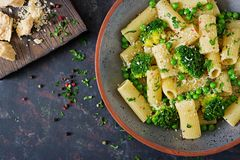 Pasta rigatoni with broccoli and green peas. Vegan menu. Dietary food. Flat lay. Top view royalty free stock images