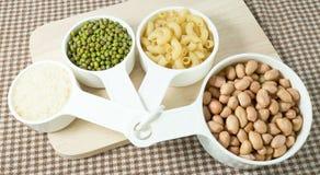 Pasta, riso, arachidi e fagioli verdi in tazze di misurazione immagine stock