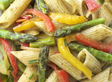 Pasta in roasted asparagus, peppers with green pesto Royalty Free Stock Photos
