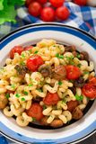 Pasta with roasted mushrooms and cherry tomatoes Stock Photos