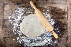 Pasta rotolata con il matterello sulla tavola di legno coperta di farina di cottura Fotografie Stock