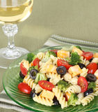 Pasta Salad. With cheese, tomatoes, black olives, broccoli and a glass of wine Stock Photo