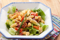 Pasta salad. A bacon, lettuce, and tomato pasta salad sits in a blue and white bistro bowl atop a colorful striped napkin stock photography