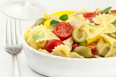 Pasta salad. Italian bow tie pasta salad with tuna, cherry tomatoes, green olives and yellow bell pepper royalty free stock photography