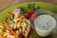 A pasta salad accompanied by a tomato and a pot of sauce stock photography