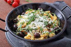 Pasta salad with arugula and olives. In metal pan stock photos