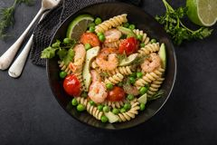 Pasta salad with avocado, shrimps, tomato and grean peas royalty free stock photography