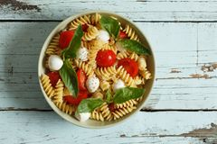 Pasta salad with cherry tomatoes and basil leaves Royalty Free Stock Photo