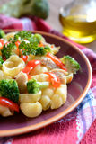 Pasta salad with chicken meat, broccoli, chilli and peppers. On a wooden background royalty free stock photos