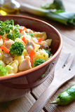 Pasta salad with chicken meat, broccoli, chilli and peppers. On a wooden background stock image