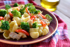 Pasta salad with chicken meat, broccoli, chilli and peppers. On a wooden background royalty free stock images