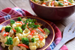 Pasta salad with chicken meat, broccoli, chilli and peppers. On a wooden background stock photography