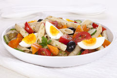 Pasta Salad with Egg. A bowl of pasta salad with egg, tomatoes, cucumber, orange pepper and olives, in a herb dressing stock photography