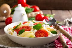 Pasta salad with fresh red cherry tomato and feta cheese. Italian cuisine. Closeup stock images