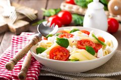 Pasta salad with fresh red cherry tomato and feta cheese. Italian cuisine. Closeup stock photography