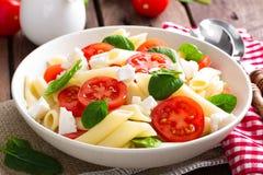 Pasta salad with fresh red cherry tomato and feta cheese. Italian cuisine Stock Photo