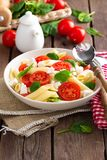 Pasta salad with fresh red cherry tomato and feta cheese. Italian cuisine Stock Image