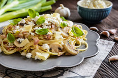 Pasta salad with fried bacon, mushrooms, green onion and cheese Stock Photo