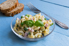 Pasta salad in a glass bowl on blue wood Royalty Free Stock Images