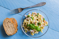 Pasta salad in a glass bowl on blue wood Royalty Free Stock Image