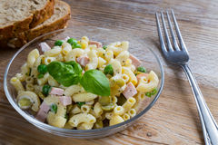 Pasta salad in a glass bowl on wood Stock Images