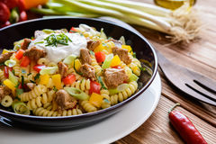 Pasta salad with pork, pepper, green onion, parsley and sour cream Stock Photo