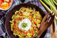 Pasta salad with pork, pepper, green onion, parsley and sour cream Stock Image