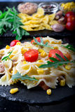 Pasta salad in slate plate with tomatoes cherry, tuna, corn and arugula. ingredients. Italian food. Pasta salad in slate plate with tomatoes cherry, tuna, corn royalty free stock photos